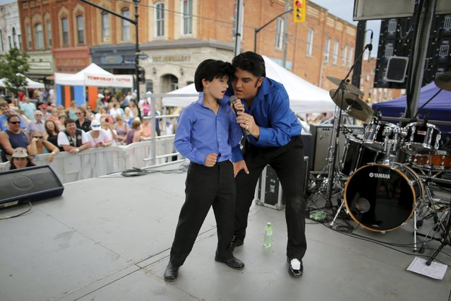 Elvis Presley tribute artist Norm Ackland, Jr of Windsor, Ontario performs with his son Jax on a street stage at the four-day Collingwood Elvis Festival in Collingwood, Ontario July 25, 2015. Ackland Jr's father was Canada's first Elvis tribute artist, starting his career in 1968. (Photo by Chris Helgren/Reuters)
