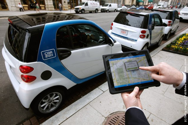 A car2go employee shows how members can use a smartphone or iPad app to locate and reservec car2go vehicles March 22, 2012 in Washington, DC