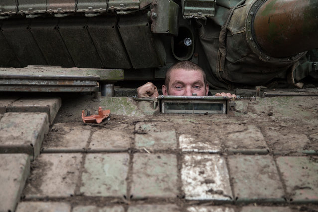 A Ukrainian serviceman looks out from a tank at a base near the village of Peski, Donetsk region, on February 16, 2015. Ukraine's army is not planning to pull its heavy weapons back from the frontline late Monday, as it is meant to do under a nascent truce, because of continued attacks by pro-Russian rebels, a military spokesman told AFP. (Photo by Oleksandr Ratushniak/AFP Photo)