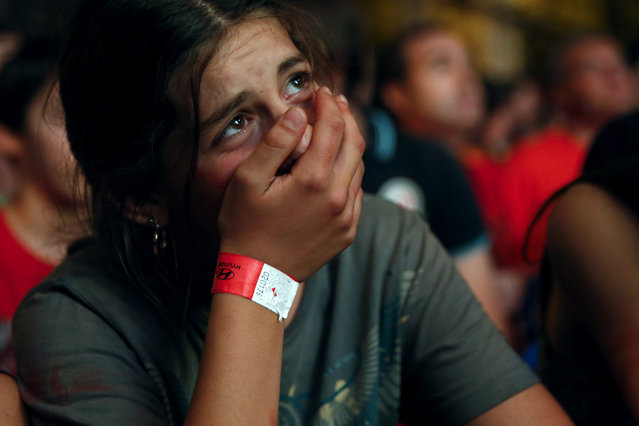 A Spain supporter cries as she watches the team's 2014 World Cup Group B soccer match against Netherlands on a giant screen at a fan park in Madrid, June 13, 2014. (Photo by Juan Medina/Reuters)