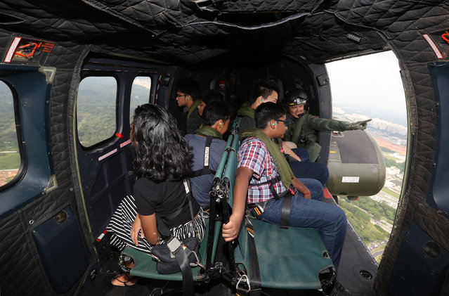 Seven beneficiaries of The Straits Times School Pocket Money Fund were given a treat on board a Super Puma helicopter on June 6, 2017 in Singapore. They were on board to watch the flypast of the state flag that was being flown by a Chinook helicopter for National Day Parade rehearsals. (Photo by Seah Kwang Peng/The Straits Times)