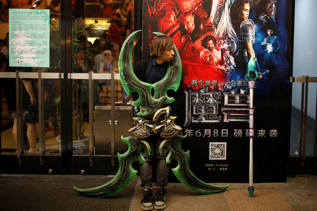 """A fan stands in front of a poster during China's premiere of the film """"Warcraft"""" at a theatre in Shanghai, China June 7, 2016. (Photo by Aly Song/Reuters)"""