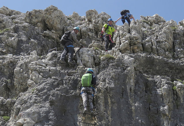 Climbers make their way up a via ferrata to the peak of Piz Da Lech in the Dolomite Mountains near the town of Corvara in northern Italy July 20, 2015. (Photo by Bob Strong/Reuters)
