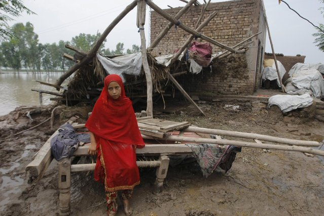 A Pakistani girl sits on remains of her house which is destroyed by floodwater in Peshawar, Pakistan, Monday, August 3, 2015. Pakistani authorities said the death toll from flash floods triggered by seasonal monsoon rains in various parts of the country has risen to more than 100. Meanwhile, floodwater has inundated vast areas, leaving tens of thousands homeless. (Photo by Mohammad Sajjad/AP Photo)