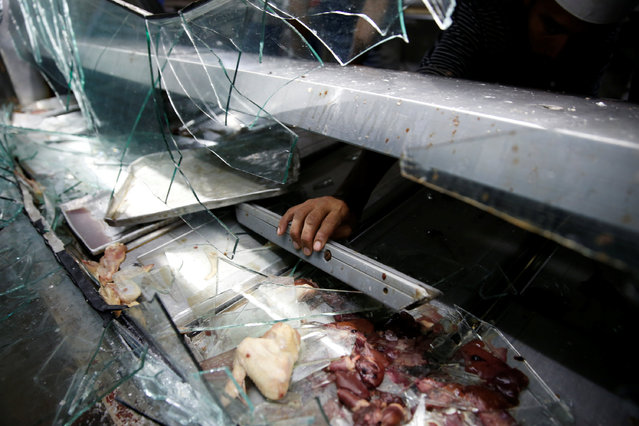 A man grabs a piece of a broken refrigerator, after a butcher's stall was looted in the slum of Petare in Caracas, Venezuela June 10, 2016. (Photo by Carlos Garcia Rawlins/Reuters)