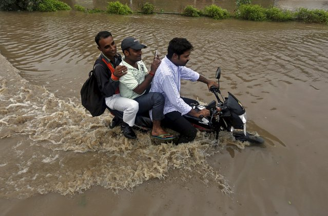 Men ride on a motorcycle through a flooded road after heavy rains in Ahmedabad, India, July 28, 2015. (Photo by Amit Dave/Reuters)