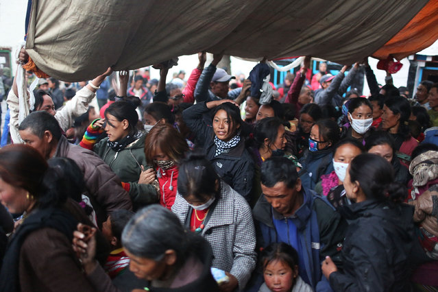 Loba men, women, and children are blessed as they walk under an enormous thangka at the end of the 2nd day of the Tenchi Festival on May 26, 2014 in Lo Manthang, Nepal. The Tenchi Festival takes place annually in Lo Manthang, the capital of Upper Mustang and the former Tibetan Kingdom of Lo. Each spring, monks perform ceremonies, rites, and dances during the Tenchi Festival to dispel evils and demons from the former kingdom. (Photo by Taylor Weidman/Getty Images)
