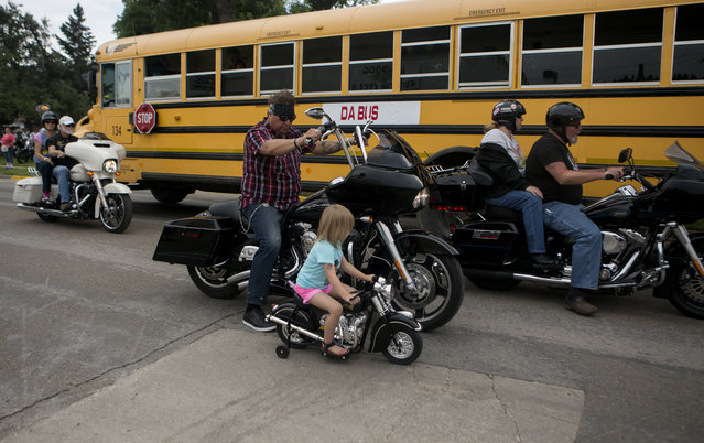 M.J. Gunderson (C), follows his 4-year-old daughter Fynn Petri-Gunderson, both of New Town, North Dakota, as she rides a toy motorcycle during the annual Sturgis Motorcycle Rally in Sturgis, South Dakota, August 4, 2015. (Photo by Kristina Barker/Reuters)