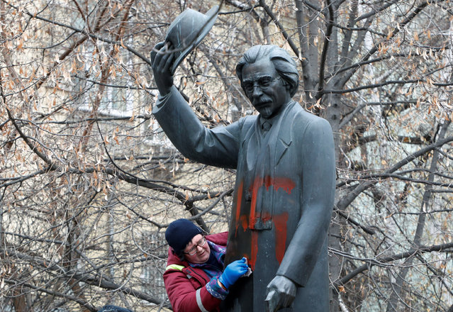 A worker cleans a monument to Yiddish author Sholem Aleichem vandalized with swastikas in Kiev, Ukraine on November 25, 2019. (Photo by Valentyn Ogirenko/Reuters)
