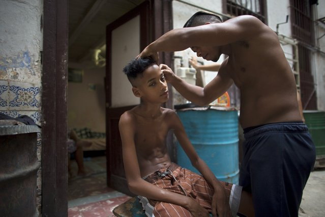 Samuel Garcia, 12, has his hair cut by a friend at the doorstep of his home in Havana, Cuba July 30, 2015. (Photo by Alexandre Meneghini/Reuters)