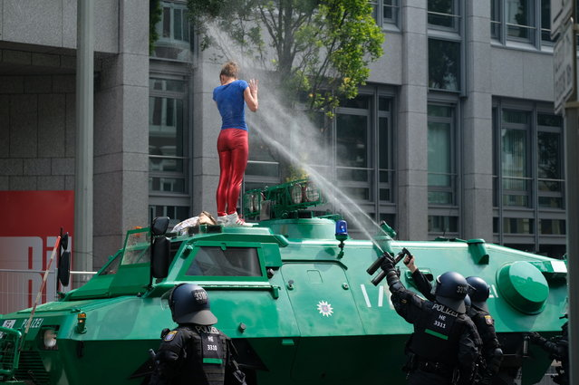 Policemen shoot pepper spray on a demonstrator who has climbed onto an armored vehicle of the police during a protest on July 7, 2017 in Hamburg, northern Germany, where leaders of the world's top economies gather for a G20 summit. Protesters clashed with police and torched patrol cars in fresh violence ahead of the G20 summit, police said. German police and protestors had clashed already on Thursday (July 6, 2017) at an anti-G20 march, with police using water cannon and tear gas to clear a hardcore of masked anti-capitalist demonstrators, AFP reporters said. (Photo by Boris Roessler/AFP Photo/DPA)