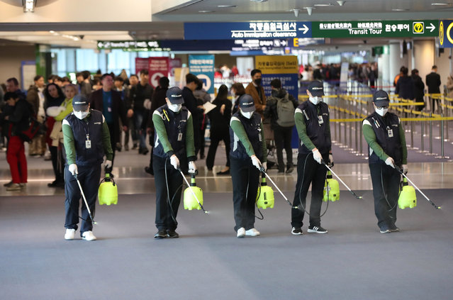 Quarantine workers spray disinfectant at Incheon International Airport, in Incheon, South Korea, 21 January 2020, to prevent the advance of a new strain of coronavirus now spreading in China and other parts of Asia. The National Quarantine Station at the airport stepped up inspections after a Chinese woman, who arrived by plane from the Chinese city of Wuhan on 19 January, tested positive for the new type of pneumonia-like disease. (Photo by Yonhap/EPA/EFE)