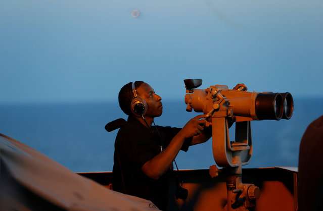 A sailor uses binoculars at sundown from the bridge of the USS Harry S.Truman aircraft carrier in the eastern Mediterranean Sea June 13, 2016. (Photo by Baz Ratner/Reuters)