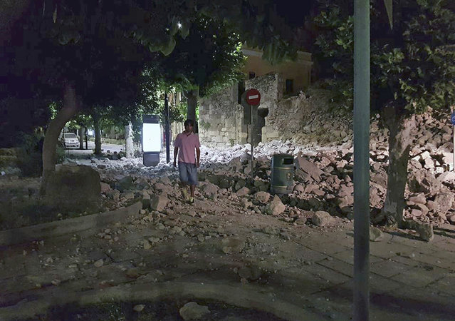 A man walks near a damaged building after an earthquake on the Greek island of Kos early Friday, July 21, 2017. A powerful earthquake struck Greek islands and Turkey's Aegean coast early Friday morning, damaging buildings and a port and killing people, authorities said. (Photo by Kalymnos-news.gr via AP Photo)