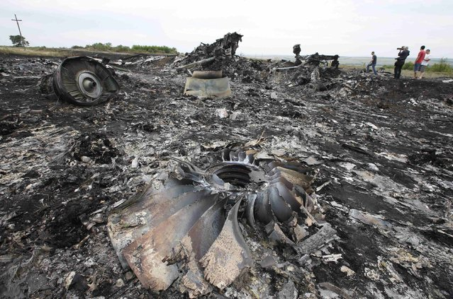 Debris is seen at the site of Thursday's Malaysia Airlines Boeing 777 plane crash near the settlement of Grabovo, in the Donetsk region July 18, 2014. World leaders demanded an international investigation into the shooting down of Malaysia Airlines Flight MH17 with 298 people on board over eastern Ukraine, as Kiev and Moscow blamed each other for a tragedy that stoked tensions between Russia and the West. (Photo by Maxim Zmeyev/Reuters)