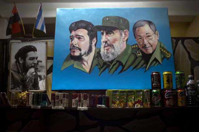 "In this July 26, 2015 photo, images of Cuban revolutionary heroes, Ernesto ""Che"" Guevara, left, Fidel Castro, center, and President Raul Castro hang on a wall at a pizzeria in Santiago, Cuba. Some advocates of U.S. travel to Cuba says they are optimistic about Santiago's future, particularly since American tourists remain barred from pure tourism and must participate mostly in cultural or educational activities well-suited to historic sites like Santiago. (Photo by Ramon Espinosa/AP Photo)"
