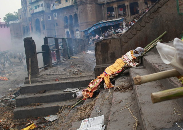 A body is left to dry prior to cremation on the banks of river Ganges in Varanasi, in the northern Indian state of Uttar Pradesh, June 19, 2014. (Photo by Danish Siddiqui/Reuters)