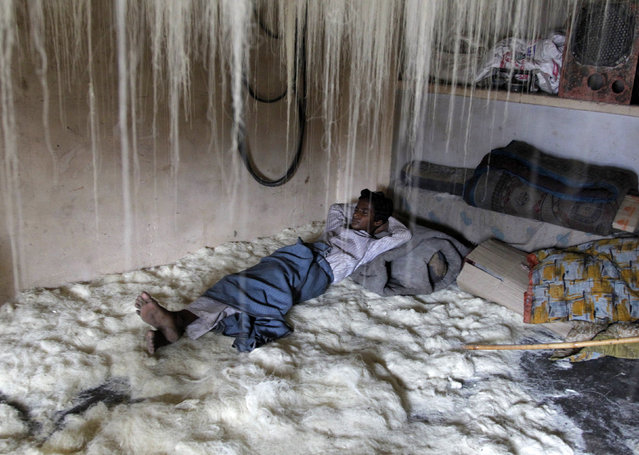 A worker rests on vermicelli inside a factory in the northern Indian city of Allahabad July 22, 2014. Vermicelli is a specialty eaten during the Muslim holy fasting month of Ramadan by many believers across the country. (Photo by Jitendra Prakash/Reuters)