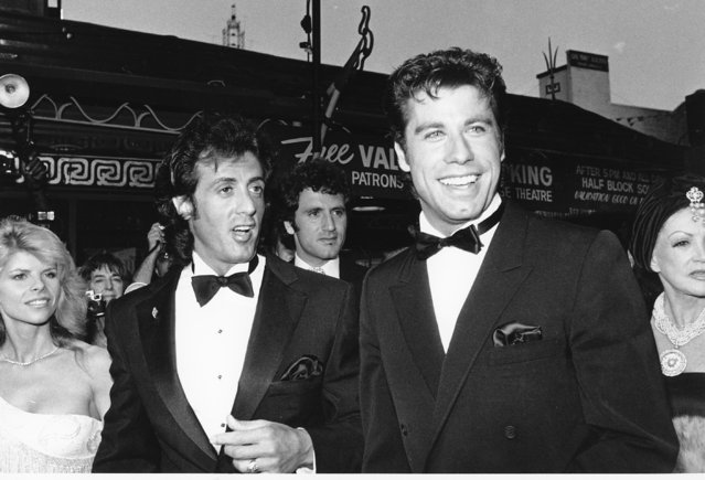 """John Travolta, right, Sylvestor Stallone and his wife, Sasha, are  seen arriving at the world premiere of their movie """"Staying Alive"""" in Hollywood, Ca., on July 11, 1983. Stallone wrote, directed and produced the movie.  The premiere is a benefit for The Stallone Fund for Autism research. Stallone's brother Frank can be seen in the background. (Photo by Nick Ut/AP Photo)"""