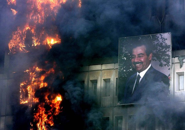 A portrait of Saddam Hussein hangs on the burning Ministry of Transport and Communication building in Baghdad Wednesday, April 9, 2003