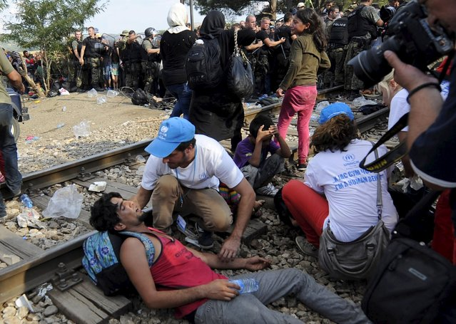 U.N. workers help a man who collapsed at the border line dividing Macedonia and Greece August 21, 2015. (Photo by Ognen Teofilovski/Reuters)