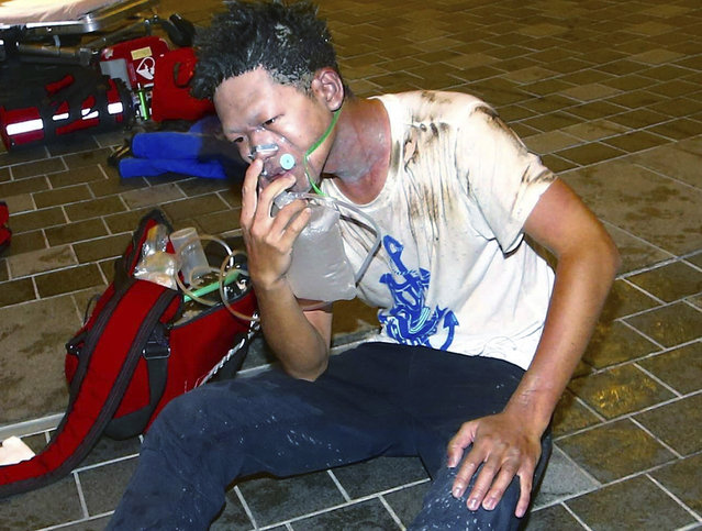 An injured man sits on the ground outside a station after an explosion on a passenger train in Taipei, Taiwan, Thursday, July 7, 2016. (Photo by Jerry Chen/AP Photo)