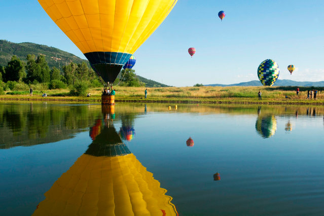 A balloon dips into Bald Eagle lake during the 36th Annual Hot Air Balloon Rodeo in Steamboat Springs, Colorado on July 9, 2017. (Photo by Jason Connolly/AFP Photo)