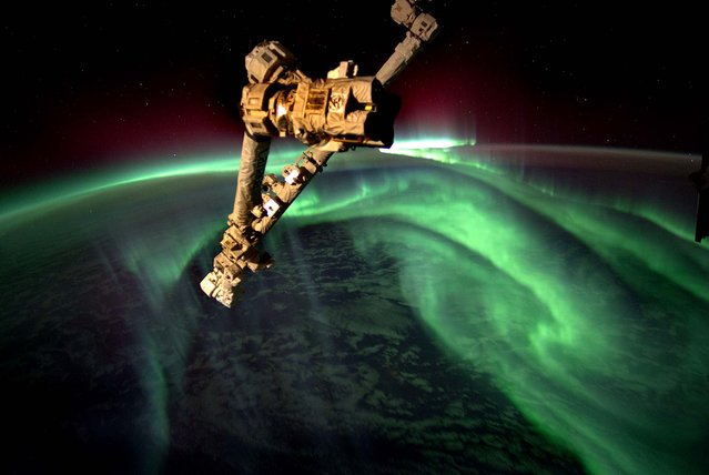This image released by NASA, taken by astronaut Joe Acaba onboard the International Space Station at an altitude of approximately 240 miles, shows the Aurora Australis, also known as the Southern Lights, on July 15, 2012. The Canadarm2 robot arm is in the foreground. (Photo by Joe Acaba/NASA)