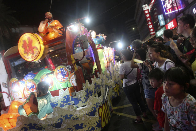 In this photo made late Saturday, August 9, 2014, in Keelung, Taiwan, onlookers watch floats decorated with folklore characters during a parade marking the beginning of the Chinese mid-summer's Ghost Month Festival. Fourteen days into the seventh month of the lunar calendar, August 9, in 2014, marks the traditional Chinese Ghost Month where the gates of the underworld are opened and spirits of the deceased are set free to roam the world of the living. The month long festivities are aimed to please the roaming spirits. (Photo by Chiang Ying-ying/AP Photo)