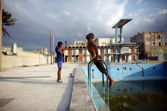 Raul Ecosegui (R), who studied to be a mechanic but now works as a carpark attendant at the U.S. Embassy in Havana, exercises next to Hansel Pupo, 24, who studied to be a veterinarian but decided to be a construction worker, in Havana, March 13, 2015. (Photo by Alexandre Meneghini/Reuters)