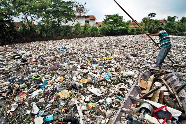 A man rows a boat on the garbage-filled Citepus River to collect reusable materials in Bandung, Indonesia, January 28, 2020. According to villagers, the Citepus River has been covered by trash since December 2019. (Photo by Septianjar/Xinhua News Agency)