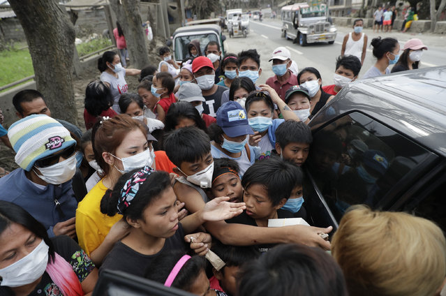 Residents scramble to grab relief goods given by a citizen at a town near Taal volcano, Tagaytay, Cavite province, southern Philippines on Sunday January 19, 2020. Many poor families living near Taal volcano have been affected due to loss of income after business closures in the area. (Photo by Aaron Favila/AP Photo)