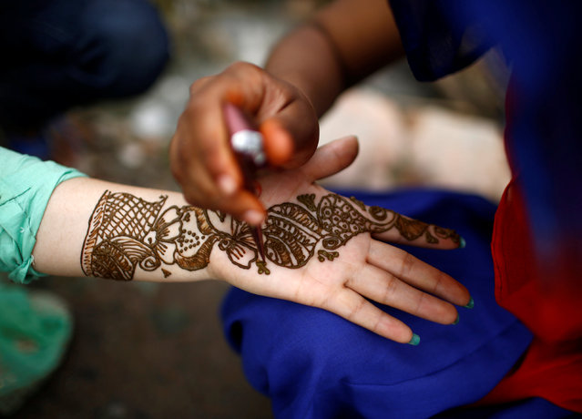 A palm of a woman is decorated with Mehndi also knows as henna tattoos during the Shrawan Sombar festival in Kathmandu, Nepal, July 18, 2016. (Photo by Navesh Chitrakar/Reuters)