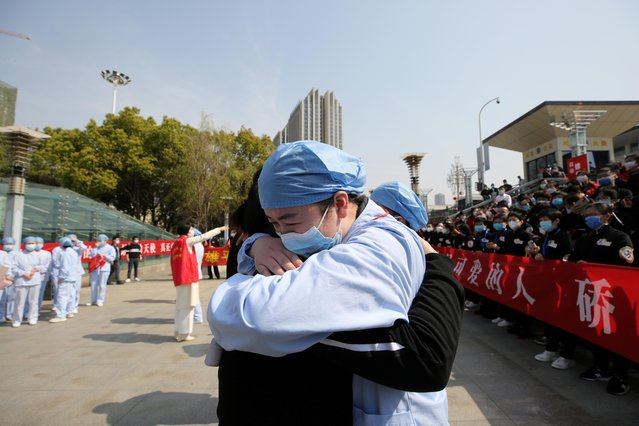 A local medical worker embraces and bids farewell to a fellow medical worker from Jiangsu at the Wuhan Railway Station as the medical team from Jiangsu leaves Wuhan, the epicenter of the coronavirus outbreak, in China's Hubei province, March 19, 2020. (Photo by Reuters/China Daily)