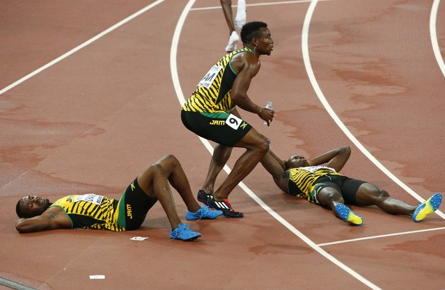 Ricardo Chambers of Jamaica (L) and his teammates Peter Matthews and Javon Francis react after finishing fourth in the men's 4 x 400 metres relay final at the 15th IAAF Championships at the National Stadium in Beijing, China August 30, 2015. (Photo by David Gray/Reuters)