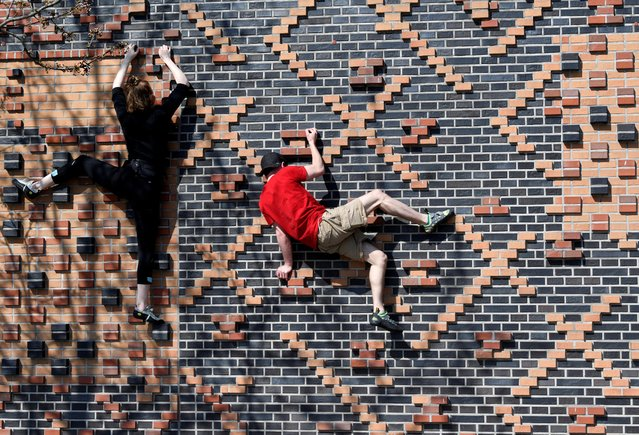Climbers Carlotta and Rafael train on a house wall in Hafencity district, as the spread of coronavirus disease (COVID-19) continues in Hamburg, Germany, April 5, 2020. (Photo by Fabian Bimmer/Reuters)