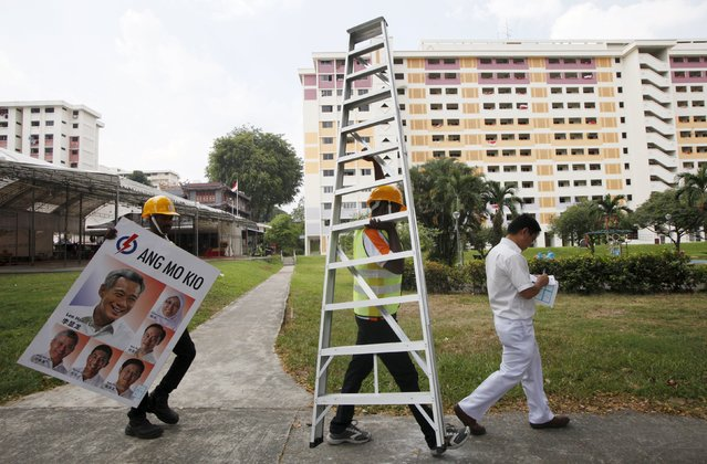 Workers prepare to put up a People's Action Party (PAP) sign on a street lamp ahead of the general election in Singapore September 1, 2015. Singapore goes to the polls on September 11, more than a year before a deadline for the next election, with the government seen riding the feel-good factor of the wealthy city-state's 50th birthday last month amid slowing economic growth. (Photo by Edgar Su/Reuters)