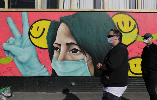 Pedestrians walk past coronavirus-themed artwork of a person wearing a mask and gloves that was painted by street artists @theydrift and @ksra_ksra on a boarded-up business in Seattle's Capitol Hill neighborhood, Tuesday, April 7, 2020. Street art has sprung up on boards covering the windows of many businesses in the area closed temporarily due to the outbreak of the coronavirus. (Photo by Ted S. Warren/AP Photo)