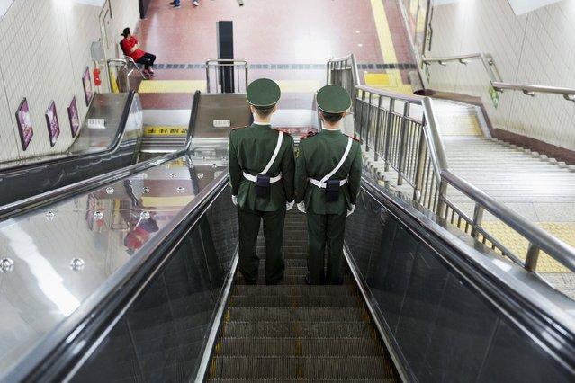 Paramilitary policemen travel on escalators under Beijing's Tiananmen Square September 2, 2015. (Photo by Damir Sagolj/Reuters)