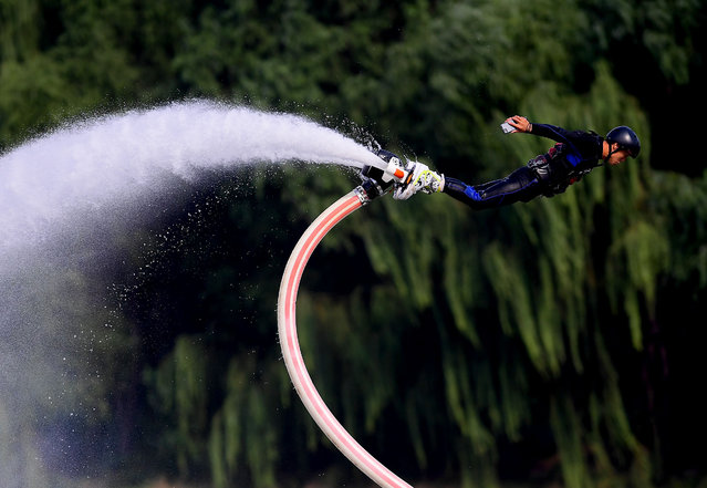 This photo taken on September 24, 2017 shows a man performing on a water-propelled flyboard at Shenyang Olympic Park in Shenyang in China's northeastern Liaoning province. (Photo by AFP Photo/Stringer)