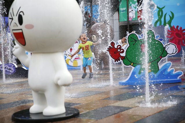 """A Chinese boy wearing a T-shirt with Chinese words """"China"""" plays among pop ups of 'Line Friends', characters of emojis from Japanese chat application Line in a shopping mall in Beijing, China, 11 August 2014. (Photo by How Hwee Young/EPA)"""