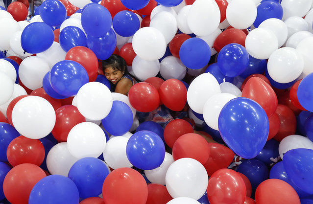 Karla Ortiz, 11, of Las Vegas, dives into balloons on the floor after the Democratic National Convention in Philadelphia, Friday, July 29, 2016. (Photo by Paul Sancya/AP Photo)