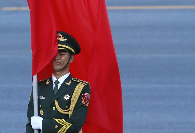 A Chinese honor guard holds a red flag during an official welcoming ceremony for Malaysia's King Abdul Halim at the Great Hall of the People in Beijing, September 4, 2014. (Photo by Kim Kyung-Hoon/Reuters)