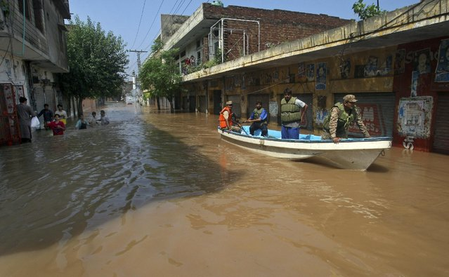 A Pakistani army soldier and volunteers use a boat in floodwater to rescue people after heavy monsoon rains in Wazirabad, some 100 kilometers (65 miles) north of Lahore, Pakistan, Sunday, September 7, 2014. (Photo by K. M. Chaudary/AP Photo)