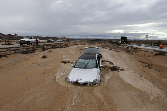 A car is partially buried in mud on Interstate 15 in Moapa, Nev., Monday, September 8, 2014. The road is closed in both directions because of the flood damage. (Photo by John Locher/AP Photo)
