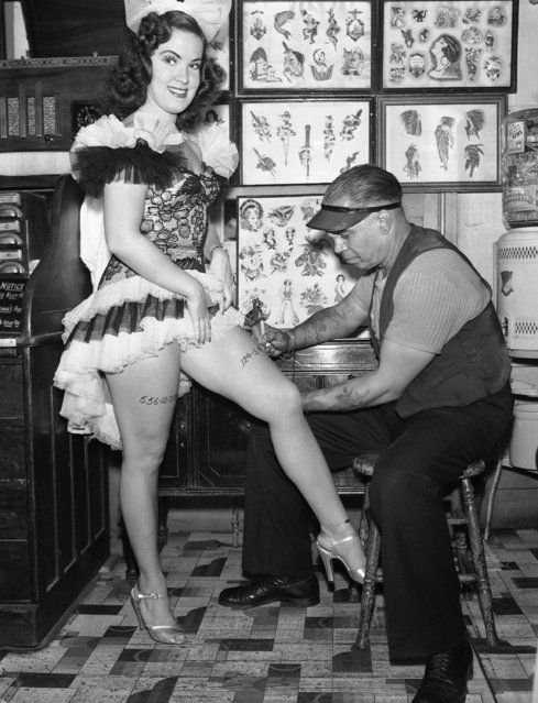 """Be prepared"" is the motto of petite Doris Sherrell, vocalist and dancer with ""Blackouts of 1942"". In the event of a bombing, the young lady had her social security number tattooed on one leg by artist Jack Julian, and address placed on the other limb for means of identification in Los Angeles, September 29, 1942. (Photo by AP Photo)"