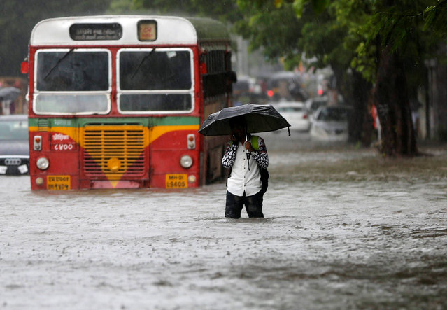 A man walks past a stranded public transport bus on a road flooded by heavy rains in Mumbai, India, August 5, 2016. (Photo by Shailesh Andrade/Reuters)