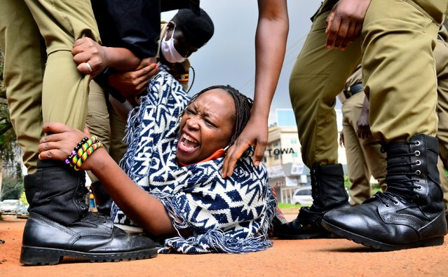 Stella Nyanzi (C), a prominent Ugandan activist and government critic, is arrested by police officers as she organised a protest for more food distribution by the government to people who has been financially struggling by the nationwide lockdown imposed to curb the spread of the COVID-19 coronavirus in Kampala, on May 18, 2020. (Photo by Abubaker Lubowa/Reuters)