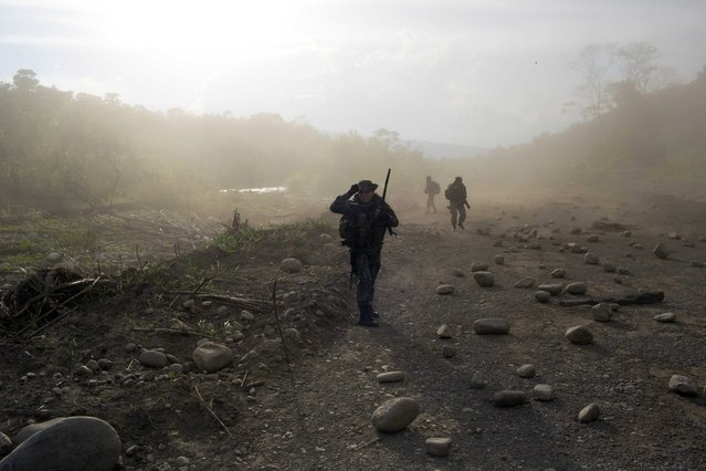 In this September 19, 2014 photo, counternarcotics officers walk in a clandestine airstrip strewn with boulders, in the Apurimac, Ene and Mantaro River Valleys, or VRAEM, the world's No. 1 coca-growing region, in Junin Peru. The boulders are used as a way to camouflage the airstrips from air observation. Security forces say that traffickers pay local villagers to keep the runways hidden and to repair them when they are cratered in counternarcotics operations. (Photo by Rodrigo Abd/AP Photo)