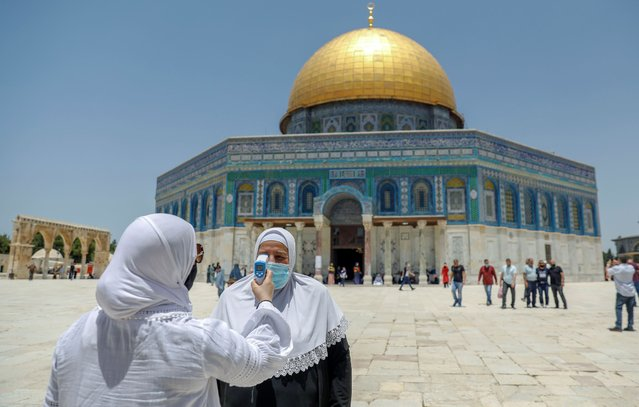 A woman checks another's temperature as Palestinian Muslims attend the first Friday prayers after a 69-day closure due to the novel coronavirus pandemic, outside the Dome of the Rock Mosque, in Jerusalem's Al-Aqsa mosques compound, on June 5, 2020. (Photo by Ahmad Gharabli/AFP Photo)